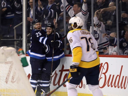 Winnipeg Jets' Paul Stastny (25) celebrates with Nikolaj Ehlers (27) after Ehlers scored, as Nashville Predators' P.K. Subban (76) skates nearby during the second period of an NHL hockey game Tuesday, Feb. 27, 2018, in Winnipeg, Manitoba. (Trevor Hagan/The Canadian Press via AP)