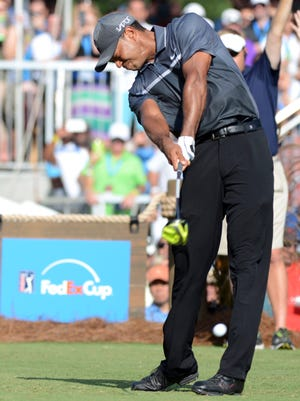 Tiger Woods hits his tee shot on the 18th hole.