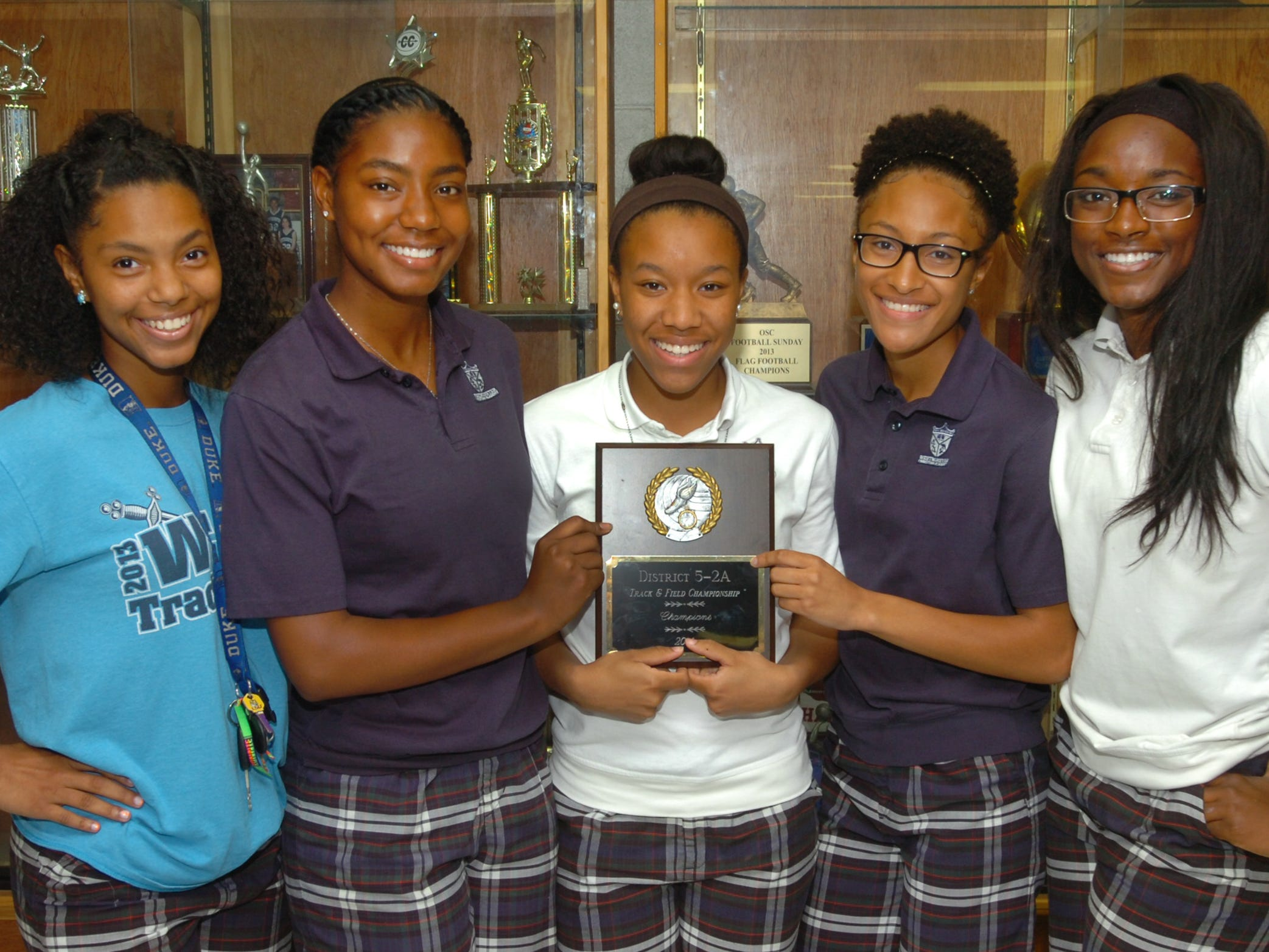 Members of the Westminster Christian girls track team celebrate the program's 10th consecutive district title.