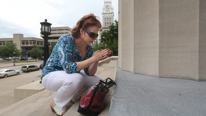 Anne Rhodes prayed on the steps of Metro Hall, in downtown Louisville. Rhodes was on hand as Jim and Jacqie Kruger blessed the Hall and the surrounding block. The Krugers are traveling to and blessing each courthouse in the state.