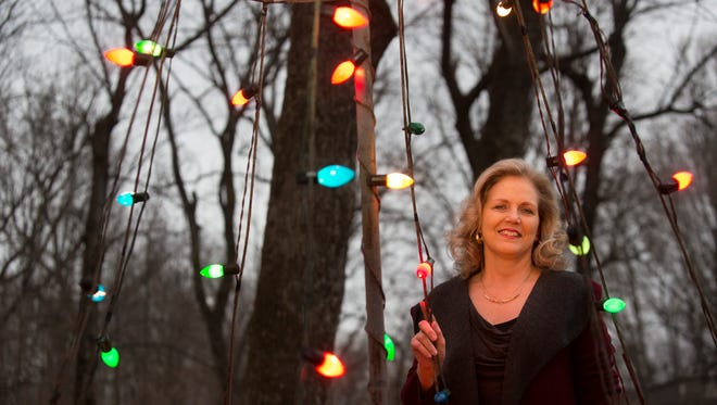 Cinda King stands with her historic metal Christmas tree that was part of her father's business for many years in Evansville. She has been reunited with the tree and it sits, lit in her yard in Louisville, Ky. Dec. 13, 2016.