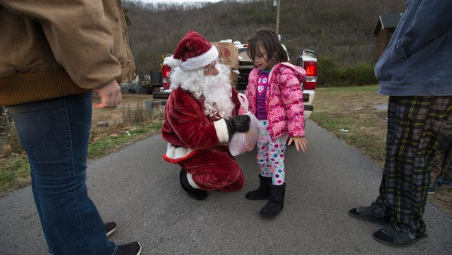 """Mountain Santa"" Mike Howard with a young girl in December 2016."