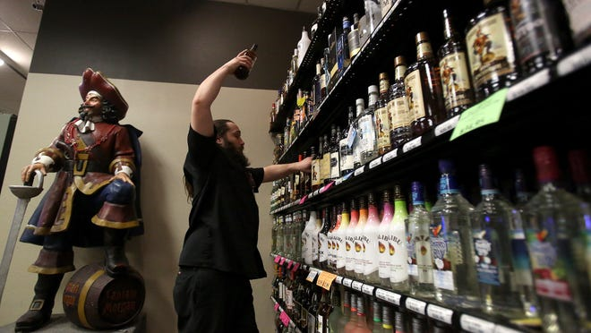 Chris Barichio stocks shelves at the Liquor Outlet on Monday in Salem. Oregon had record-breaking liquor sales in 2014 of $531.6 million, 4.3 percent more than 2013.