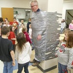 "Bucyrus Elementary School Principal Todd Roll was ""suspended"" in the lunch room by students on April 4 as a reward for meeting and exceeding the annual Right to Read Week ""Reading Challenge."""