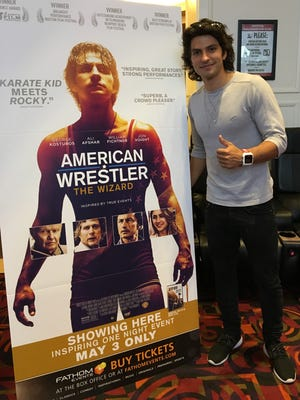 """George Kosturos, a 2010 Palm Desert graduate, stands next to a sign for the movie """"American Wrestler: The Wizard"""" in which he stars."""