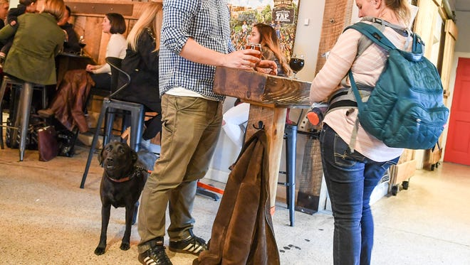 Henry, left, a black lab with owners Michael and Ellen Glen of Greenville, stands quietly while others are seated at The Community Tap near downtown Greenville on Friday.