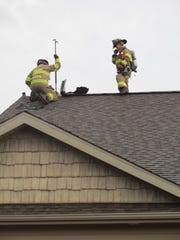 Firefighters battle a house fire at a North Liberty home that was struck by lightning Monday morning.