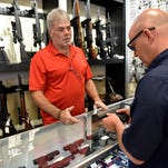 Randy Crocker (left) with USA Pawn, shows Hal Finch of Madison a pistol Tuesday in the store on I-55 at McDowell Road in Jackson. Mississippi has removed the 7 percent state sales tax on guns, ammunition, archery equipment and some hunting supplies for the first weekend each September.