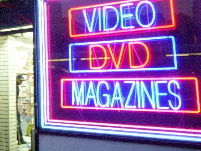 Neon signage on the front of an adult bookstore.