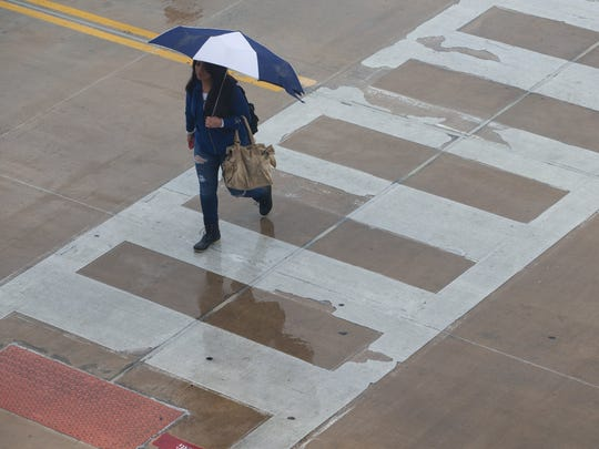 A student holds an umbrella as she walks at Texas A&M University-Corpus Christi during a rain storm.