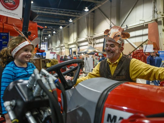 Riley McLaughlin smiles at her grandafather, Garth Everett, as she sits on a tractor at the 100th Pennsylvania Farm Show in Harrisburg, Pa. on Saturday, Jan 9, 2015. Everett is a Republican member of the Pennsylvania House of Representatives.