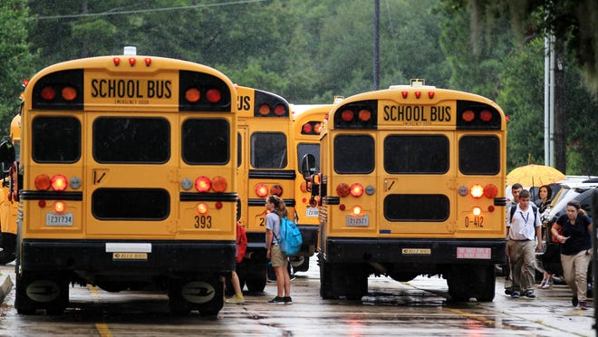 Students board their school buses at L.J. Alleman Middle School Thursday, August 21, 2014, in Lafayette, La.