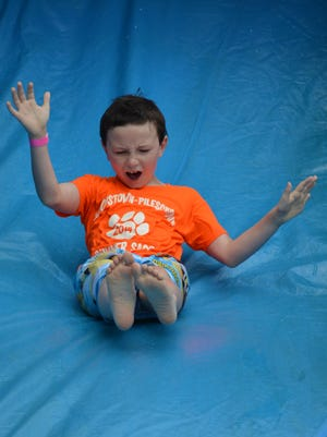 Sean Opperman, 9, of Pittsgrove bounces down an inflatable water slide at Christmas in July at Parvin State Park on Saturday, July 22. Photo/Jodi Streahle