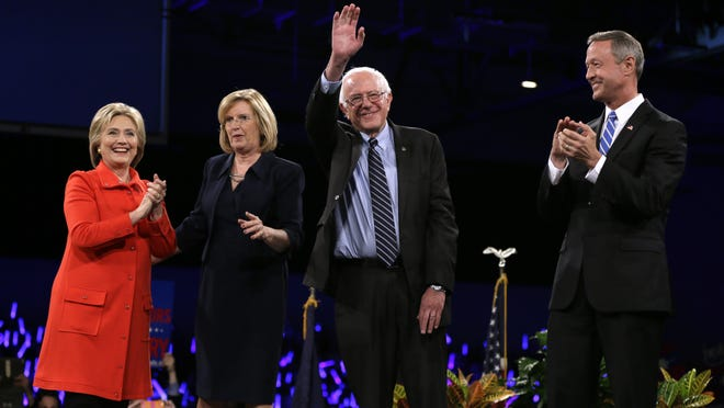 Democratic presidential candidates Hillary Rodham Clinton, left, Sen. Bernie Sanders, I-Vt., second from right, and former Maryland Gov. Martin O'Malley, right, stand on stage together at the start of the Iowa Democratic Party's Jefferson-Jackson Dinner Saturday in Des Moines, Iowa. Iowa Democratic Party chair Andy McGuire, second from left, looks on.