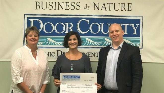 Laura Harper, middle, receives the award from Caleb Frostman, right, director of the Door County Economic Development Corporation, and Tara Carr, left, representative of the University of Green Bay Small Business Development Center.