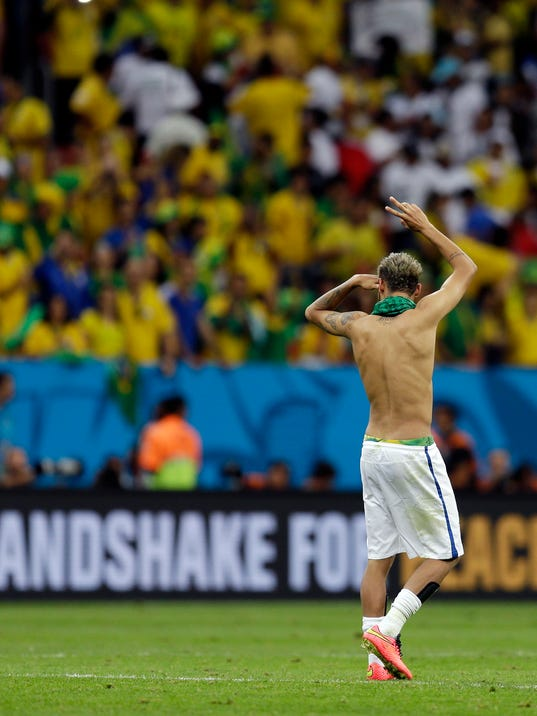 Brazil's Neymar waves to supporters following their 4-1 victory over Cameroon in the group A World Cup soccer match between Cameroon and Brazil at the Estadio Nacional in Brasilia, Brazil, Monday, June 23, 2014. (AP Photo/Natacha Pisarenko)