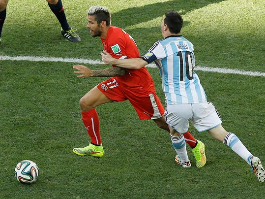 Argentina's Lionel Messi, right, holds Switzerland's Valon Behrami during the World Cup round of 16 soccer match between Argentina and Switzerland at the Itaquerao Stadium in Sao Paulo, Brazil, Tuesday, July 1, 2014. (AP Photo/Thanassis Stavrakis)