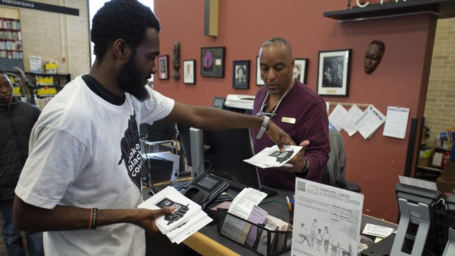 """Neal Whetstone, policy aide for Austin City Council Member Natasha Harper-Madison, hands librarian Byron Miller a stack of """"Make Black Count"""" pamphlets during a stop to the Carver Branch Library in February. The effort seeks to remind residents in hard-to-count areas to participate in the census."""