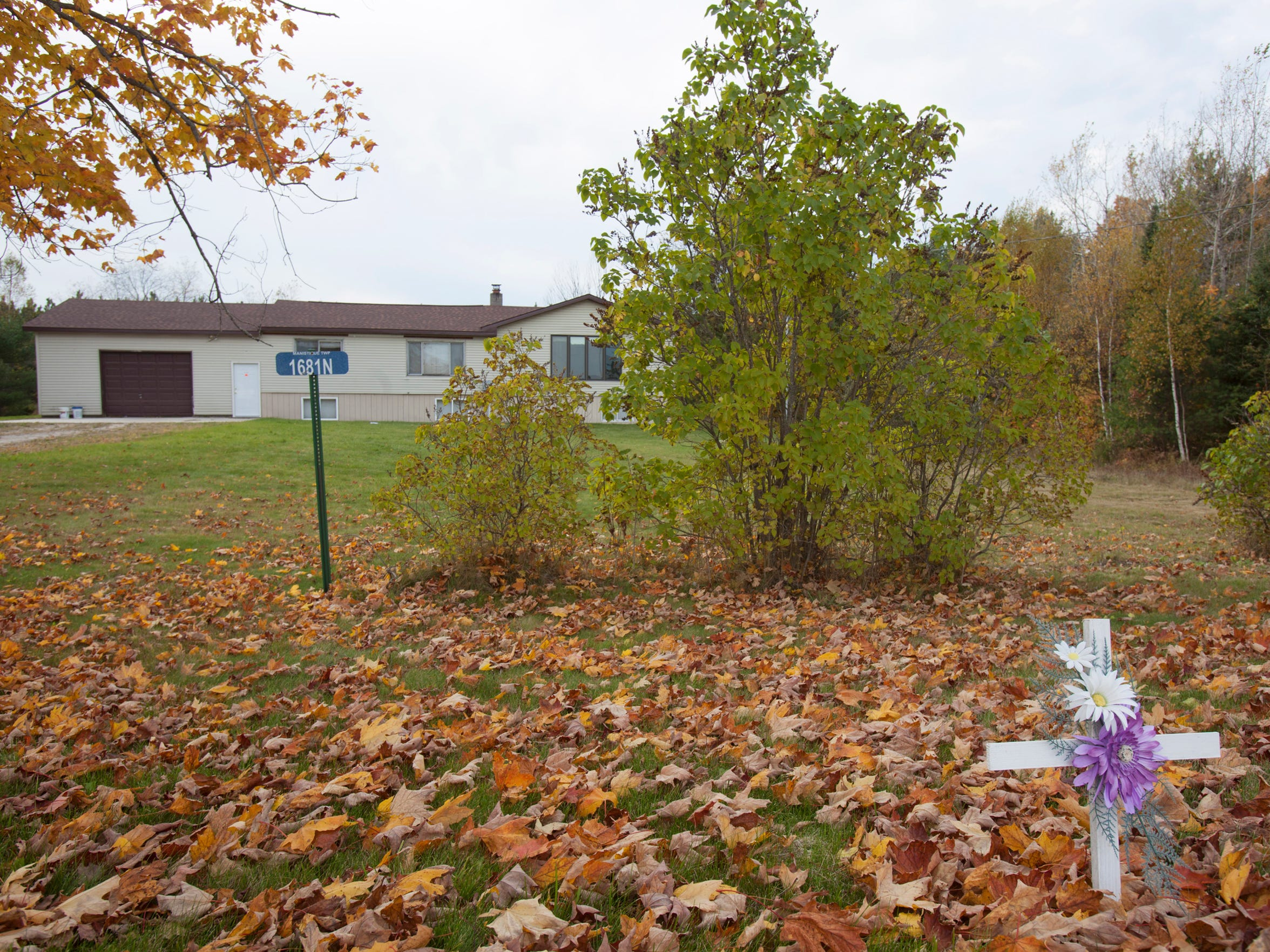 A small memorial stands in front of Kenneth Brunke's home outside of Manistique where police say the three victims were strangled and suffocated.