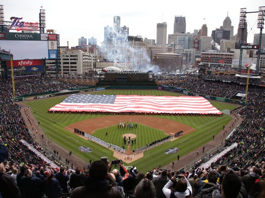 Fans stand as a large American flag is draped across
