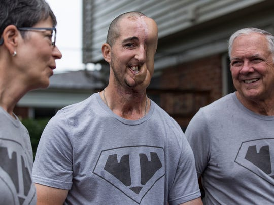 Tim McGrath of Sterling Heights, center, poses for a photo with his father Greg Mc Garth, right, and mother Kathy McGarth, both of Sterling Heights, at their home, Wednesday, July 12, 2017 in Sterling Heights.