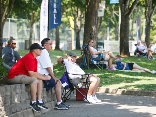 Spectators watch the USA Softball 18A National Championship from the shade on Wednesday, Aug. 2, 2017, at Wallace Marine Park in Salem, Ore. Temperatures at the Wednesday tournament reached triple digits in the afternoon.