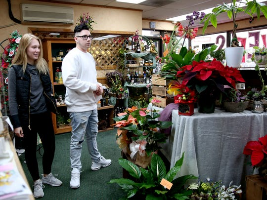 Maylie Alexander, a K12 sophomore, and Todd Daily, a McNary sophomore, buy tickets a few hours before SnoBall at Lollypops and Roses flower shop in Salem on Saturday, Dec. 2, 2017.