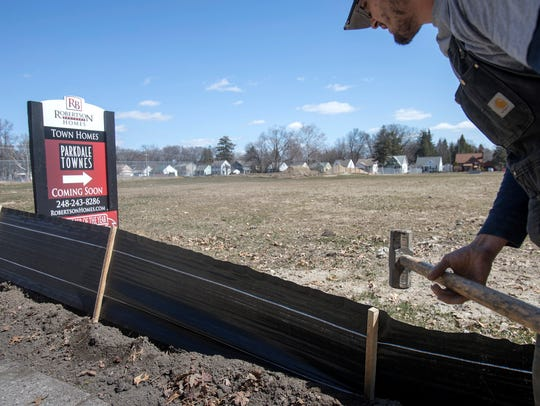 Jeff Craft, 27, of Flint sets up a barrier along the future site of the Parkdale Townes in Ferndale on Wednesday, April 5, 2018.