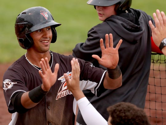Salem-Keizer's Jose Layer (15) high-fives teammates in the dugout after scoring in the Hillsboro Hops vs. Salem-Keizer Volcanoes baseball game at Volcanoes Stadium in Keizer on Thursday, July 5, 2018.