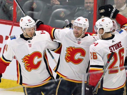 Calgary Flames center Matt Stajan (18) celebrates his goal against the Ottawa Senators with defensemen Brett Kulak (61) and Michael Stone (26) during the third period of an NHL hockey game in Ottawa, Friday, March 9 2018. (Fred Chartrand/The Canadian Press via AP)