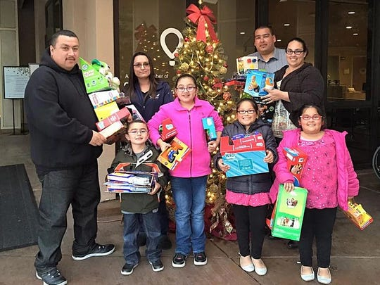 More than 1,000 toys were collected and more than 100 custom cars were on display at the inaugral Salinas Cars for Kids Car Show and Toy Drive. Joey Garcia (far left) his family and some volunteers help deliver donated toys after last year's event.