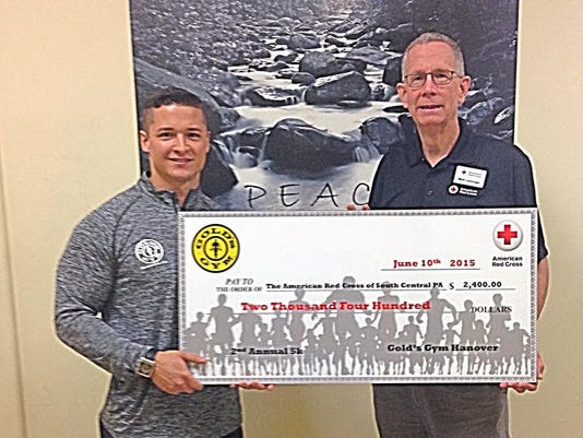 Gold s Gym Hanover General Manager Chris Simoncini, left, presented Red Cross South Central PA Chapter Executive Matt Leininger with a check for $2,400 that represented the money raised during a 5K Road Race held last month in Hanover.