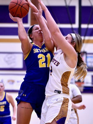 Bethany's Hannah Ferguson (21) goes up for a shot over Kansas Wesleyan's Kelcey Hinz (1) at Mabee Arena on Tuesday night.