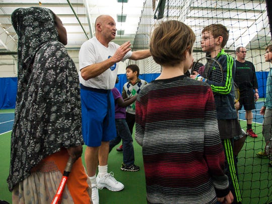 Long-time tennis teacher and coach Jake Agna speaks with young players in South Burlington on Wednesday, March 30, 2016.
