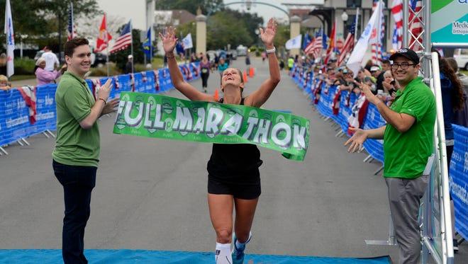 Shannon Beale crosses the finish line as the first female marathon finisher Sunday, November 12, 2017 during the Pensacola Marathon.