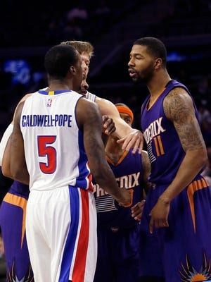 Detroit Pistons forward Jonas Jerebko, center, breaks up Pistons guard Kentavious Caldwell-Pope (5) and Phoenix Suns forward Markieff Morris (11) during the first half of an NBA basketball game in Auburn Hills, Mich., Wednesday, Nov. 19, 2014.