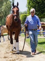 Trainer Bob Baffert walks Triple Crown winner American