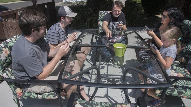 Mike Bartram, center, his wife Sabrina, and their children, from left, Bryson, 20, Jaden, 16, and Gwen, 6, play cards on the front yard patio of their home in Lodi.