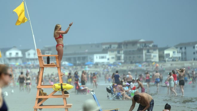 Hampton Beach lifeguard Annie Rademacher blows her whistle and signals to swimmers to come back toward shore as she watches over her area of the beach on Thursday.