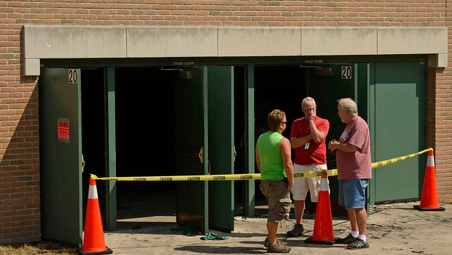 School staff members linger near the side doors to the main gymnasium at Green Bay Preble High School in Green Bay on Friday. A fire in the bleachers caused extensive damage to that part of the school and smoke damage throughout the building.