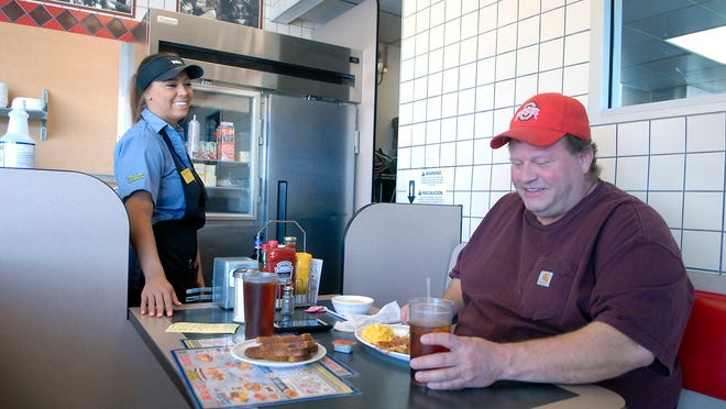 Waffle House server, Dallas Watkins, checks in with patron, David Valiquette on Fern Valley Road in the Edgewood neighborhood. April 23, 2015