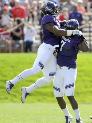 Northwestern defensive lineman Ifeadi Odenigbo (7) and linebacker Anthony Walker Jr. (1 ) celebrate a sack against Illinois State during the first half at Ryan Field.
