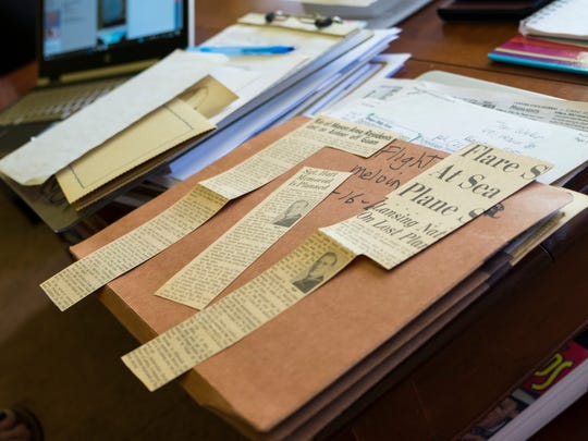 Newspaper clippings about the plane accident that killed Donna Ellis' father, Melvin Lewis Hatt, sit on Donna's living room table May 12. The plane was on its way to Vietnam when it went down.