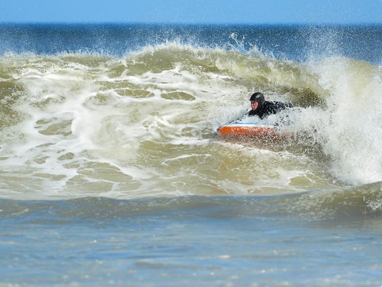 Surfers take advantage of warm weather and large waves