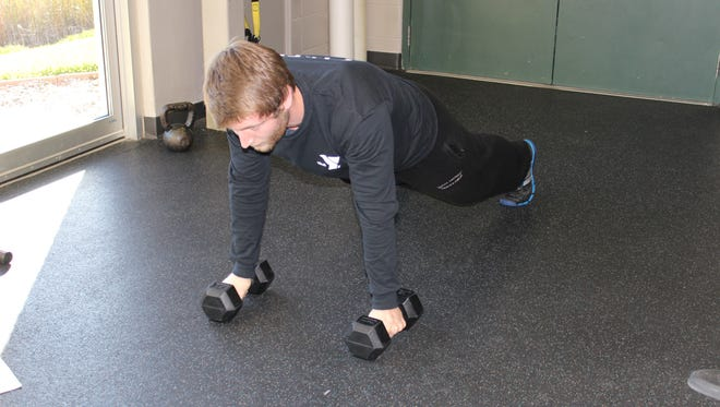 Begin in a plank position on the floor with a straight back and forward gaze.