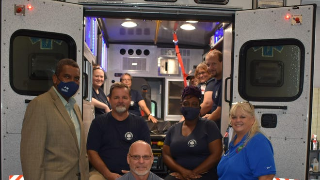Pictured are: (Front Center)  Tim Kowalewski, Vehicle Maintenance Director;(Front Row, Left to Right)  Councilman Dr. Roy Hollingsworth, Paramedic/Emergency Services Director Chris Altman, Paramedic/Crew Chief Ranata Ford, and County Administrator Rose N. Dobson-Elliott;(Left Inside Ambulance Compartment, Front to Back)  EMT-B Sarah Poock and EMT-B Robin McMillan;(Right Inside Ambulance Compartment, Front to Back)  Paramedic/Deputy Director/Training Officer Andrew Farmer,  EMT-B Delena Bradshaw, and Paramedic Brandon O'Quinn.