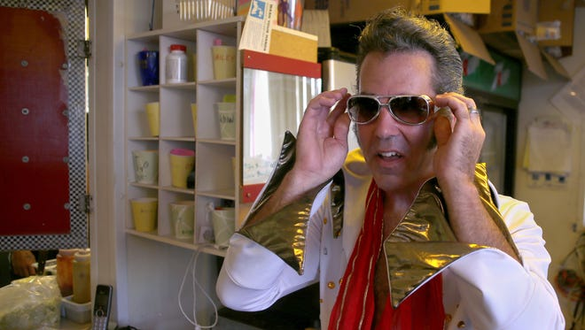 Carl Mann, co-owner of Charlie's Drive-In in Hortonville, slips on sunglasses to complete his Elvis costume. The drive-in will celebrate Elvis Day and its 50th anniversary on Tuesday and Wednesday.