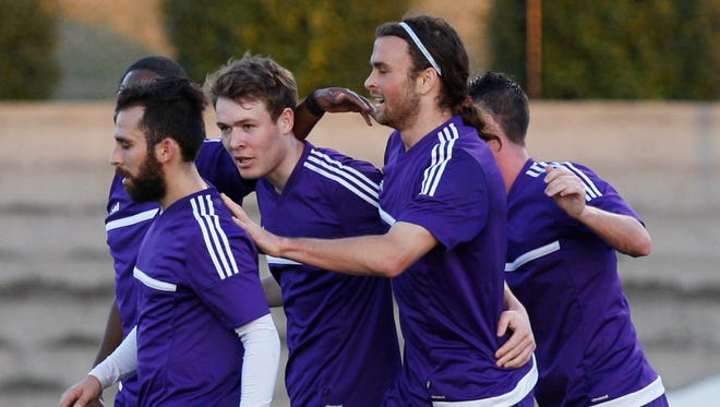Louisville FC's Magnuss Rasmussen, center, was congratulated by teammates Juan Guzman, left, and Matt Fondy, right, after he scored their first goal against U of L during their soccer match at U of L.March 11, 2015