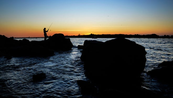 As the sun sets, fishermen ply the waters of the Indian River near Sebastian Inlet State Park Oct. 12.