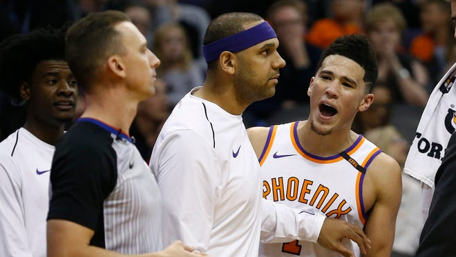 Phoenix Suns guard Devin Booker, right, is held back by teammate Jared Dudley, middle, as Booker argues his final foul with referee Justin Van Duyne, left, during the second half of an NBA basketball game against the Memphis Grizzlies, Tuesday, Dec. 26, 2017, in Phoenix. The Suns defeated the Grizzlies 99-97.